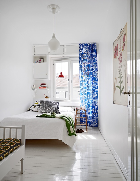 an airy minimal Scandinavian bedroom with a white bed, built-in storage units and bright textiles