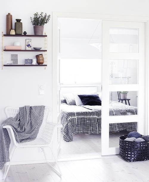 a small Nordic bedroom with a white bed, graphic bedding, skylights and chairs as nightstands