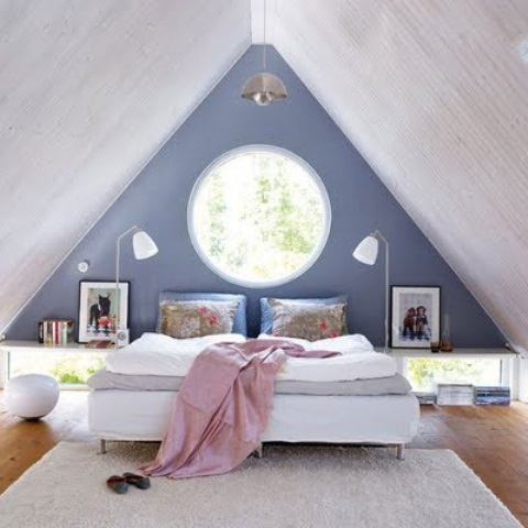 an attic bedroom with a blue and gray walls, wooden attic, a white bed, a carpet and some skylights and windows
