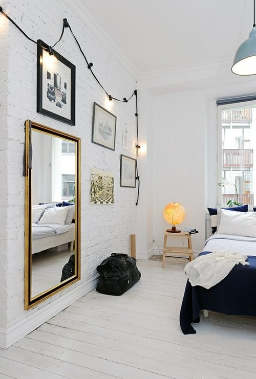 a Nordic bedroom with white brick walls, a gallery wall with mirrors and artworks, a bed and step stools as nightstands