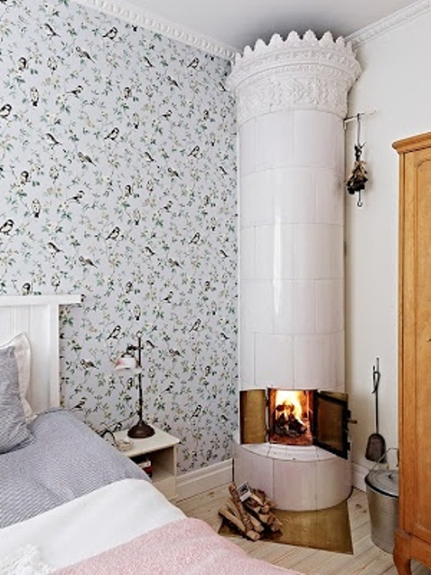 an airy Nordic bedroom with floral wallpaper, a white stove and pastel bedding