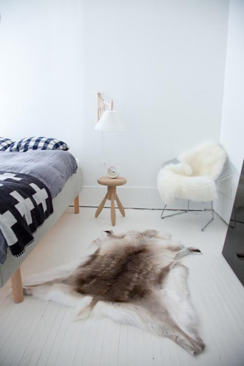 a Nordic bedroom with a wooden bed, graphic bedding and lots of faux fur for coziness