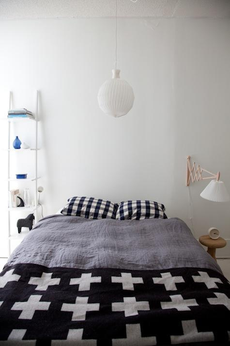 a Scandinavian bedroom with simple minimal furniture, graphic bedding and a pendant lamp