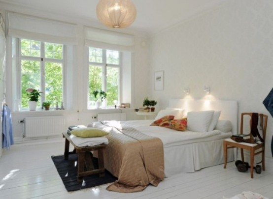 an airy Scandinavian bedroom with all things white, a pendant lamp and colorful textiles