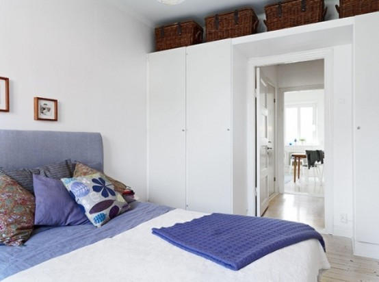 an airy Scandinavian bedroom in white, with purple touches, sleek storage units and baskets for storage