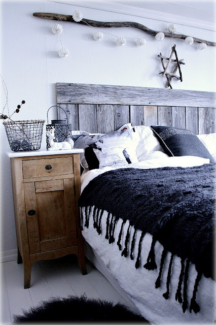 a Nordic bedroom with a weathered wood bed, a rustic wooden nightstand, lights over the bed and baskets
