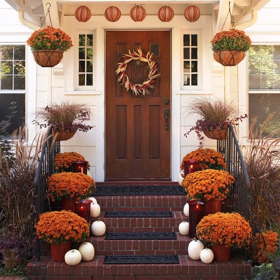 white pumpkins, bold fall blooms in pots, candle lanterns and a garland of paper pumpkins plus a fall wreath of corn and corn husks