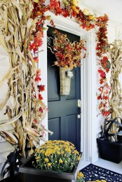 corn husks, bold fall leaves, berries and faux pumpkins, bold fall blooms in baskets and a faux fruit and veggie arrangement in a basket