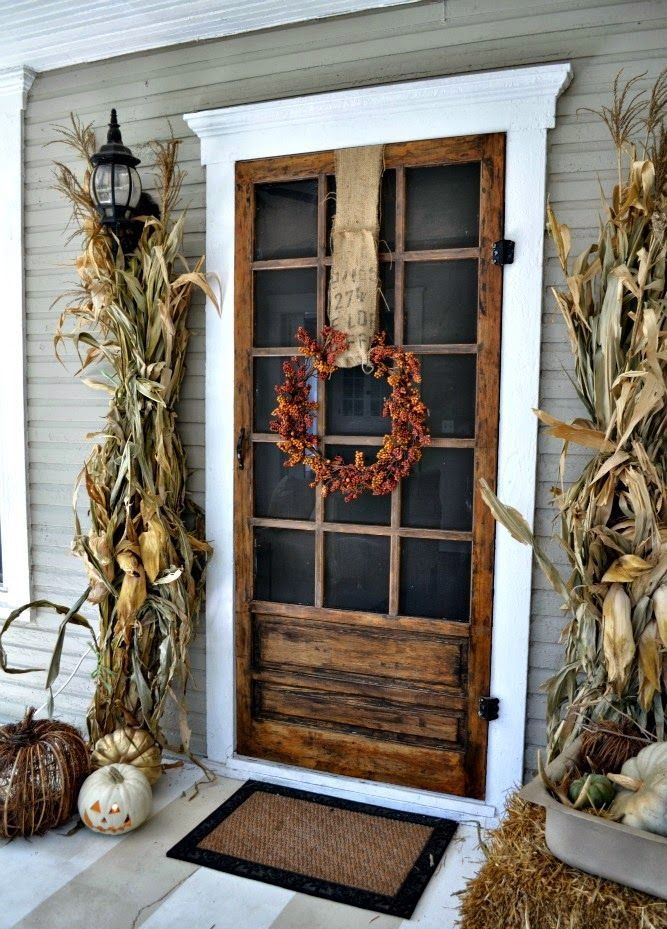 corn husks, vine and natural neutral pumpkins plus a bright pinecone and burlap wreath make up a rustic front front for Thanksgiving