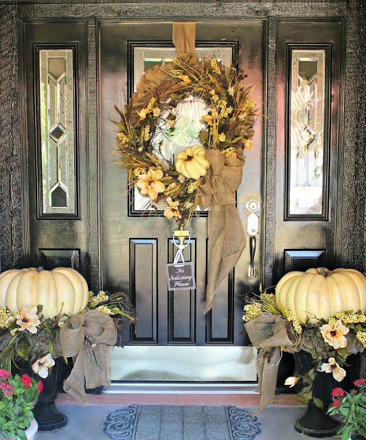 neutral oversized heirloom pumpkins in urns, neutral blooms, a wreath fo neutral pumpkins, blooms, herbs and greenery make up a cool rustic Thanksgiving front door