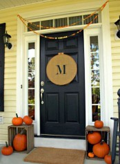 simple Thanksgiving decor with a colorful paper garland, a burlap monogram sign and crates with natural orange pumpkins
