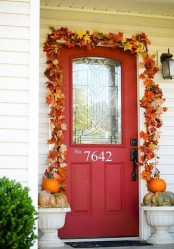 a super bright fall leaf garland over the door and some pumpkins in urns make the front door stylish and fall-like