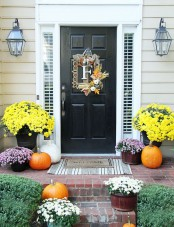 a whimsy framed F wreath with greenery and pumpkins, bright fall blooms in pots and orange and white pumpkins