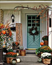 a sign, bold fall blooms in baskets, heirloom pumpkins, branches with berries and a lush floral and pumpkin arrangement