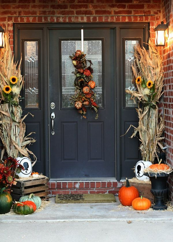 corn husks and sunflowers, orange and green pumpkins and a decoration made of faux pumpkins and foliage for a Thanksgiving front door