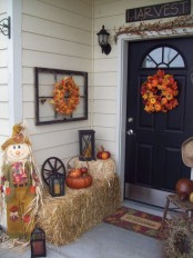 hay,, a scarecrow, candle lanterns, a fall leaf garland and wreath with pumpkins make up a rustic vintage Thanksgiving front porch