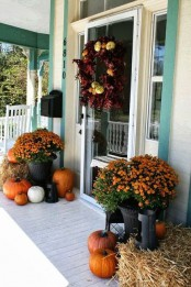orange and white pumpkins, hay, candle lanterns and a bold fall wreath of faux pumpkins and purple fall leaves