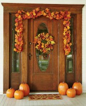orange pumpkins and a lush fall leaf garland with pumpkins and berries over the door for a stylish Thanksgiving front door
