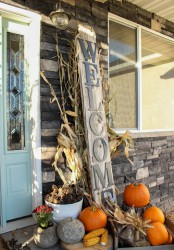 natural orange pumpkins, pinecones, corn, wheat, corn husks and a large Welcome sign for a rustic Thanksgiving porch