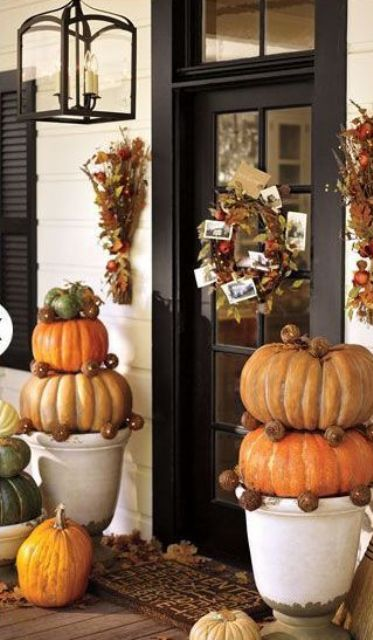 stacks of pumpkins, fall leaf arrangements and wreaths with lights create a cozy ambience in the porch