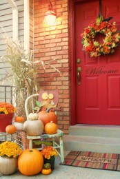 bright fall pumpkins, bright fall blooms in pots, corn husks and a wreath of bold fall leaves on the door