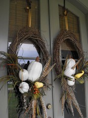 vine wreaths of white pumpkins, berries, foliage and feathers will make your front door feel more fall-like and Thanksgiving-like
