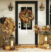 gold hay, leaves, pumpkins, candle lanterns with acorns, vine pumpkins make the front door sunny and cozy