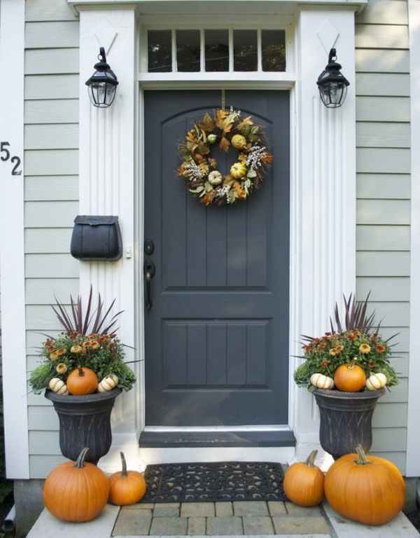 greenery and bloom arrangements with pumpkins, feathers, pumpkins on the floor and a fall wreath of feathers, foliage and pumpkins on the door
