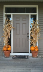 simple pot arrangements with orange pumpkins and corn husks will accent your front door and hint on Thanksgiving