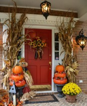corn husk arrangements, natural pumpkin stacks, bold fall blooms and candle lanterns and a faux bloom arrangement on the door for a rustic feel