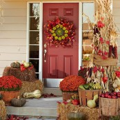 baskets with bold fall blooms, fruits and veggies, corn and corn husks, a wreath of fall leaves and green apples for Thanksgiving