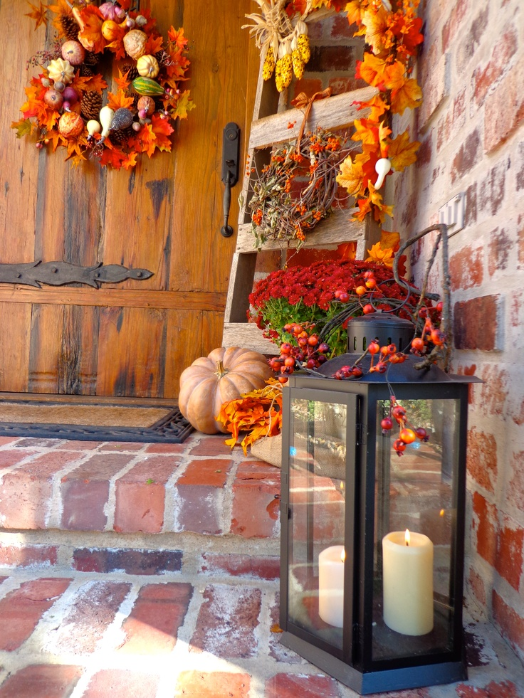 a candle lantern, faux pumpkins and leaves, a lush wreath of fall leaves, pumpkins and pinecones for Thanksgiving