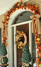 a chic and preppy Thanksgiving front door with faux pumpkins and leaves, burlap bows and a lush wreath of leaves, pumpkins and berries