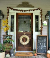 a pinecone garland, a fall leaf arrangement, a fall sign, natural pumpkins and candle lanterns for a Thanksgiving front door and porch