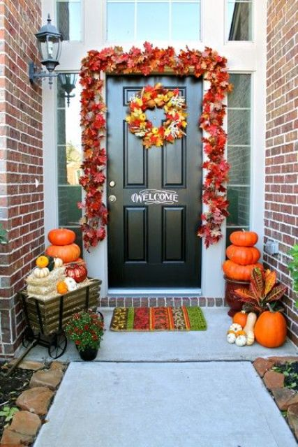 a bright fall leaf garland and wreath, stacks of pumpkins, hay, gourds and greenery for a chic front door