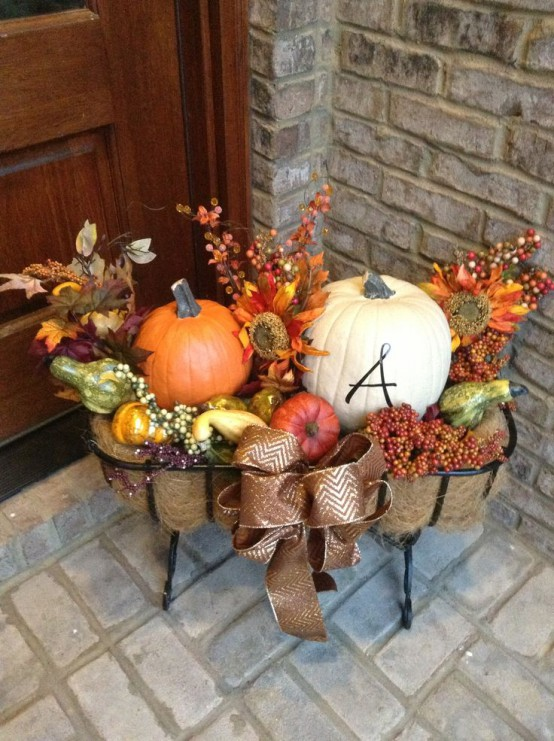 Combine traditional autumn decorations like pumpkins, colorful fall leaves, twigs with berries, and a little burlap to create a pleasing outdoor Thanksgiving arrangement.