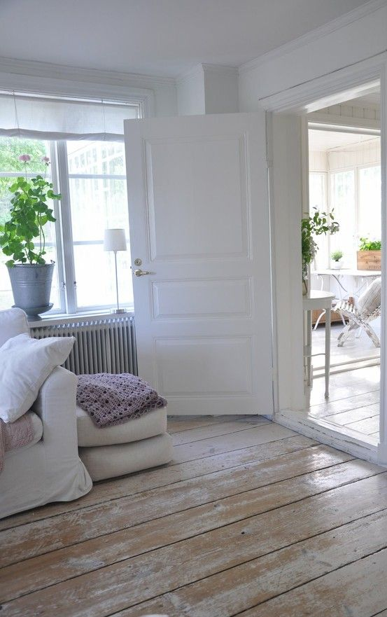 a Scandinavian space with wooden whitewashed shabby floors that give a nonchalat touch to the space