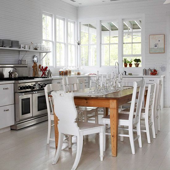 a modern white kitchen with white cabinets and walls, with a whitewashed floor, white chairs and a stained dining table