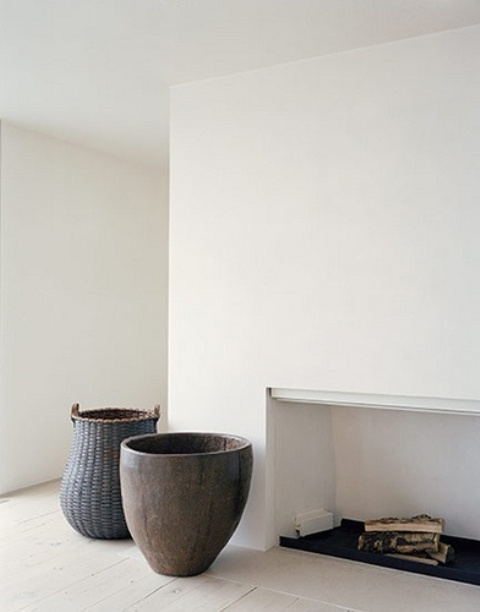 a minimalist living room with a fireplace, white walls and a whitewashed floor plus contrasting vases and pots