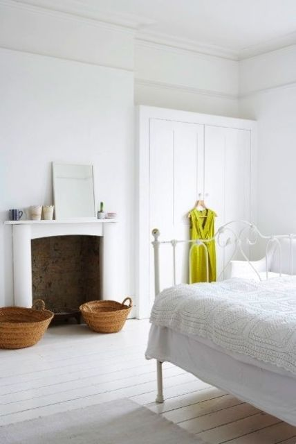 a white vintage bedroom with white walls and whitewashed floors, a non-working fireplace and white furniture