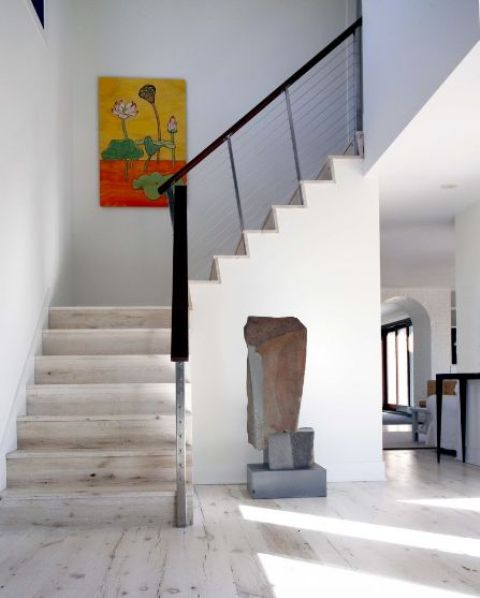 a chic foyer with a bright artwork, white walls and a whitewashed floor and matching stairs