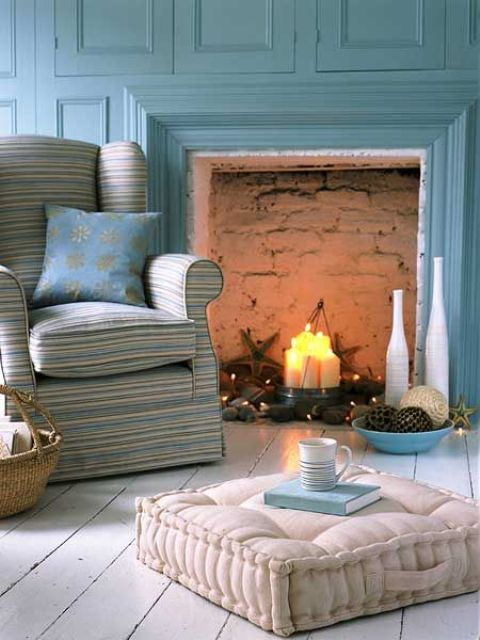 a cozy farmhouse living room in blue, with chic and comfy furniture, with a fireplace and a whitewashed floor to refresh the color scheme