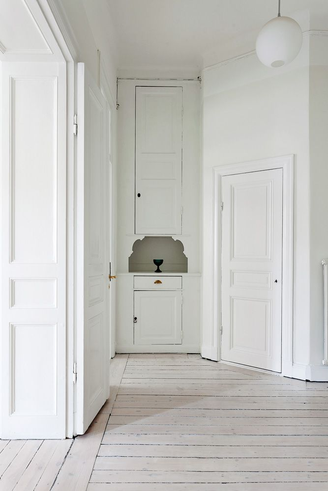 a refined white space with a whitewashed floor and softens the space a bit and gives it a warm touch