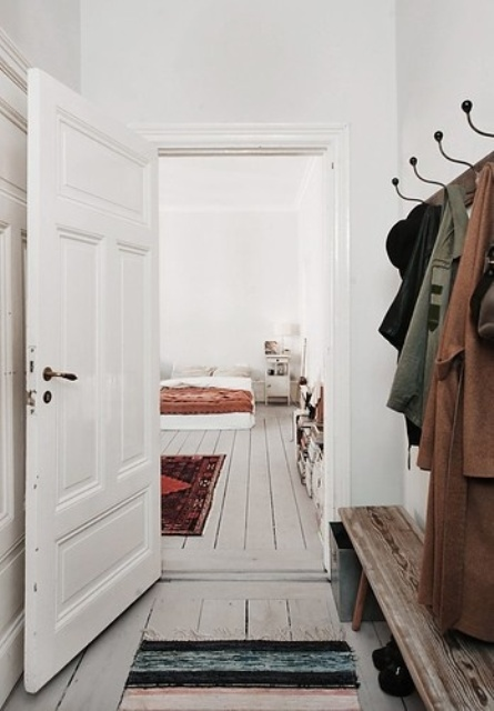 a chic Nordic space with white walls and doors and whitewashed floors to make the space softer and cozier