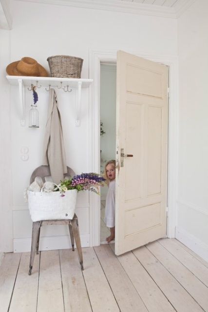 a vintage entryway with white walls, doors and a whitewashed floor that brings a relaxed touch to the space