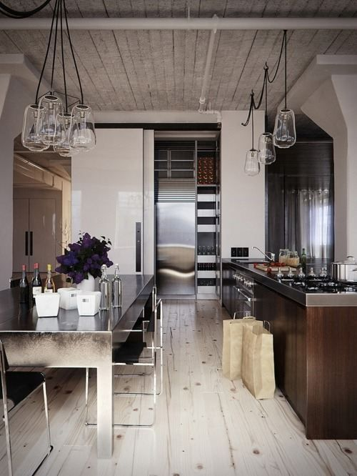 a contrasting kitchen with a whitewashed floor and ceiling and dark furniture plus pendant glass lamps