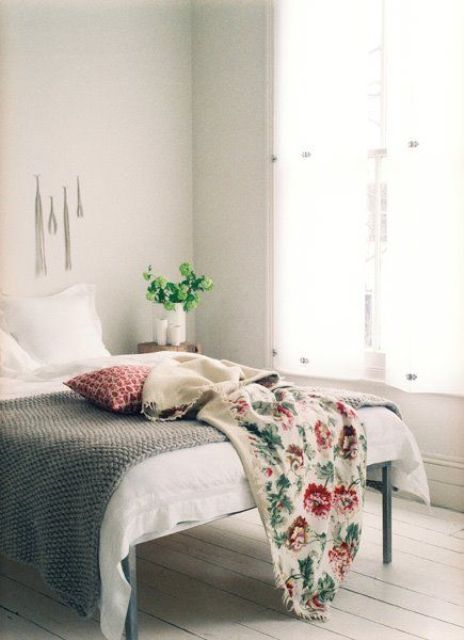 a neutral vintage bedroom with whitewashed floors, a simple bed and bright bedding plus potted greenery