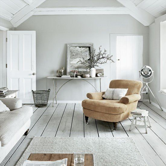 an all-white Nordic living room with white walls, a whitewashed wooden floor, neutral furniture and a tan chair for a touch of color