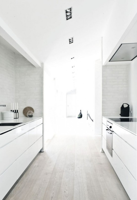 a white minimalist kitchen with a whitewashed floor, sleek cabinets and a white tile backsplash