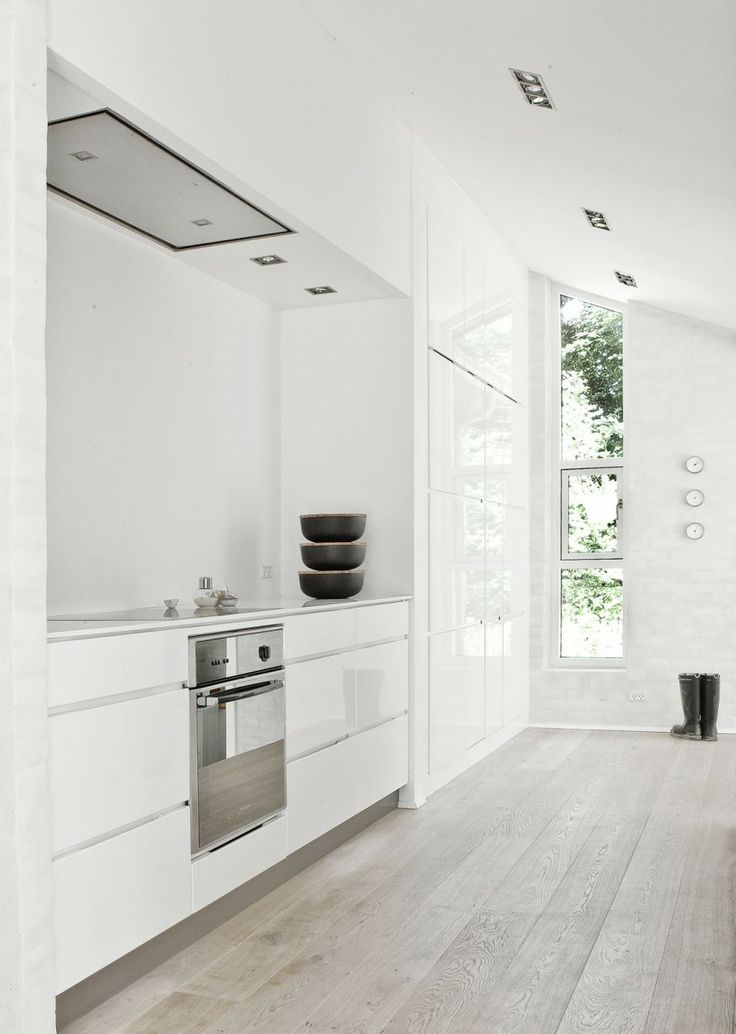 a white minimalist kitchen with whitewashed wooden floor that brings a bit of a natural touch and warmth to the space